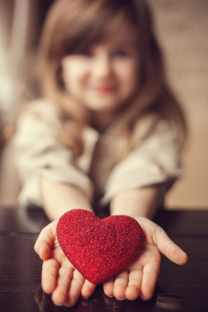 happiness symbol: Valentine Day - dreaming cute child with red Heart in hands.