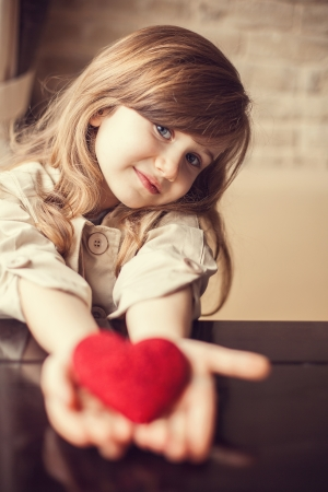 Valentine Day - dreaming cute child with red Heart in hands.