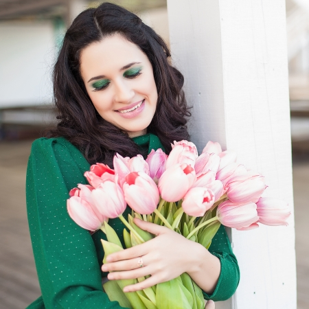Beautiful young brunette woman with pink tulips