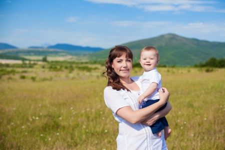Family - happy mom and her son smiling at nature photo