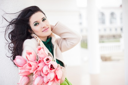Beautiful young brunette woman with pink tulips photo