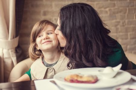 family health: Mom and young daughter eating breakfast