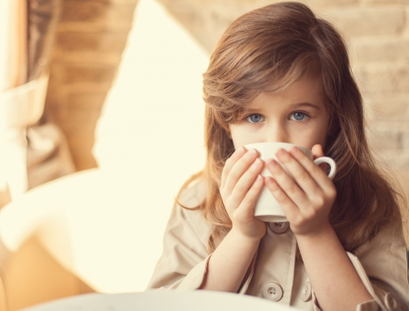 happy little girl indoors eating and smiling photo