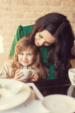 Mom and young daughter eating breakfast photo