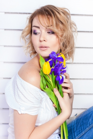 Elegant fashionable woman with flowers over wall background photo