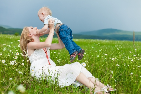 Smiling mother and little son on nature. Happy people outdoors photo