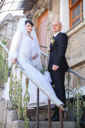 happy newly married couple standing on vintage stairs outside photo