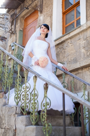 Beautiful bride portrait on stairs in white dress with a bouquet of flowers photo