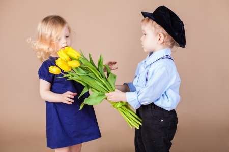 Funny kids, happy little boy giving a cute girl bouquet of yellow spring flowers. Series in studio Stock Photo - 18061285