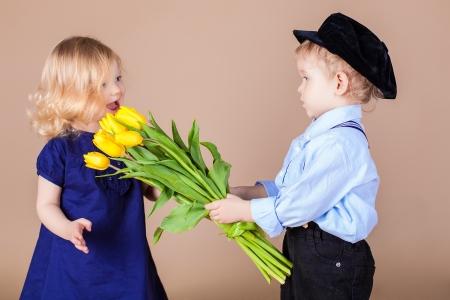 Funny kids, happy little boy giving a cute girl bouquet of yellow spring flowers. Series in studio Standard-Bild