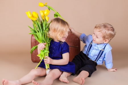 Funny kids, happy little boy giving a cute girl bouquet of yellow spring flowers. Series in studio Stock Photo - 18061356