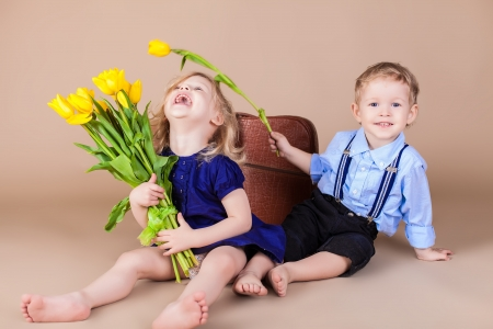 Funny kids, happy little boy giving a cute girl bouquet of yellow spring flowers. Series in studio Stock Photo - 18061443