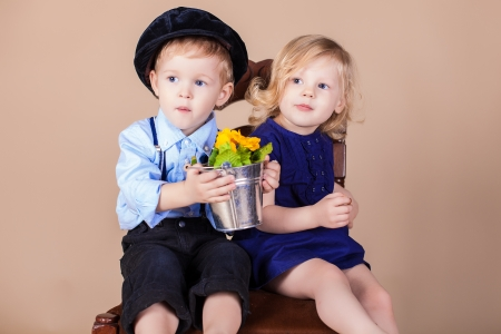 Funny kids, happy little boy giving a cute girl bouquet of yellow spring flowers. Series in studio photo