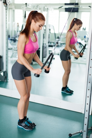 Attractive young fitness model works out on training apparatus inside in fitness center Stock Photo - 19045548