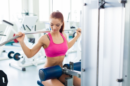 workout gym: Attractive young fitness model works out on training apparatus inside in fitness center