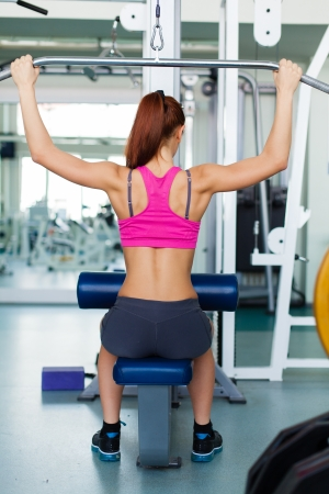 Attractive young fitness model works out on training apparatus inside in fitness center Stock Photo - 19045550