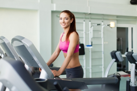 Attractive young fitness model runs on a treadmill, is engaged in fitness sport club