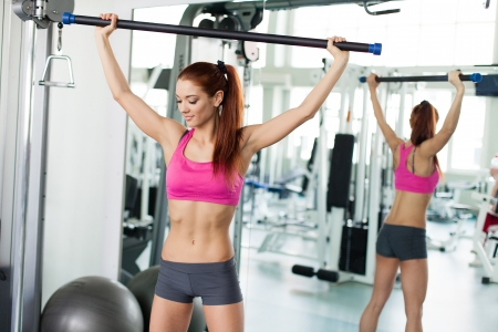 Attractive young fitness model exercising in fitness sport club photo