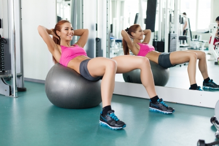 Attractive young fitness model workout with gymnastic ball inside in fitness center photo