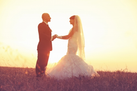 Young couple in love bride and groom on sunset background photo