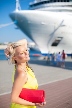 Beautiful Vacationing Woman in a dock, big cruise ship on background photo