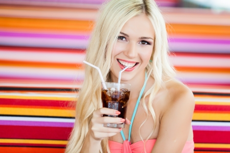 beautiful young blond woman in swimsuit on vacation at the beach with a cocktail photo