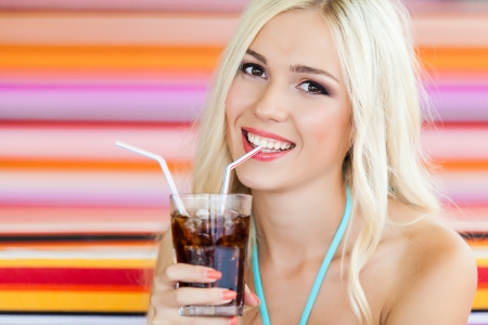 beautiful young blond woman in swimsuit on vacation at the beach with a cocktail Stock Photo