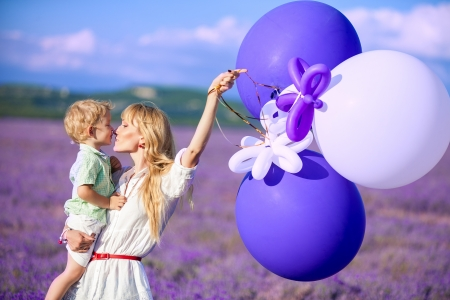 lavanda: Mother and son playing with balloons on beautiful summer day Stock Photo
