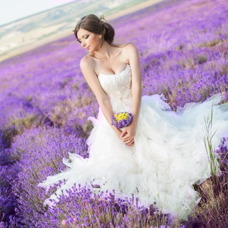 purple dress: Beautiful bride posing at field of lavender LANG_EVOIMAGES
