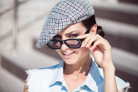 Close-up portrait of a beautiful smiling girl wearing a hat and nerd glasses photo