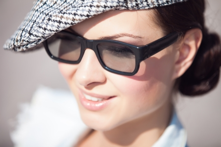 Close-up portrait of a beautiful smiling girl wearing a hat and nerd glasses
