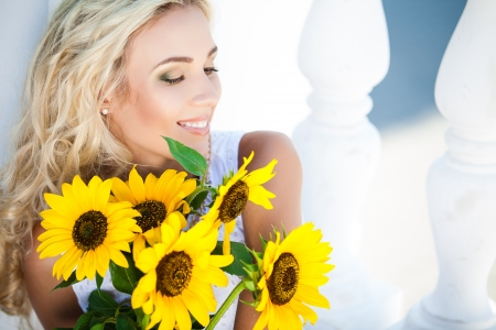 Close-up portrait of attractive woman with sunflowers in her hand Stock Photo