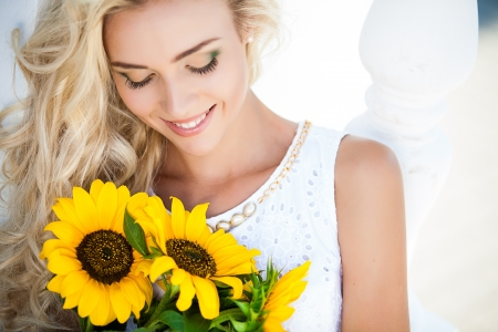Close-up portrait of attractive woman with sunflowers in her hand Imagens