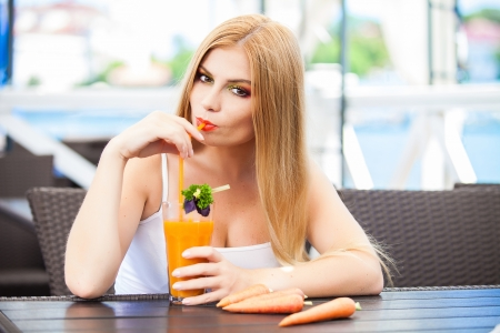 Lovely smile relaxing woman drinking freshly squeezed carrot juice in a restaurant photo