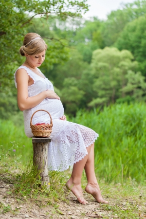 Happy pregnant woman in the green park on lake Stock Photo