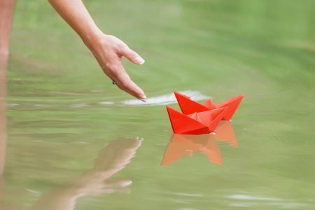 hand and paper boat in river photo