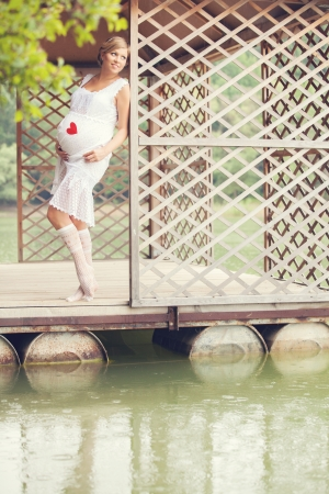 attractive young pregnant woman is resting in the gazebo on the lake photo