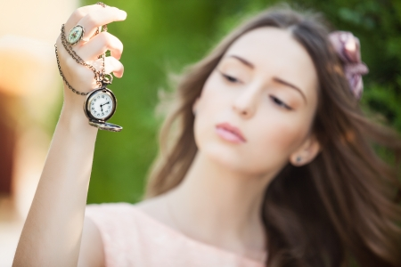 Portrait of young attractive woman with a clock on chain photo