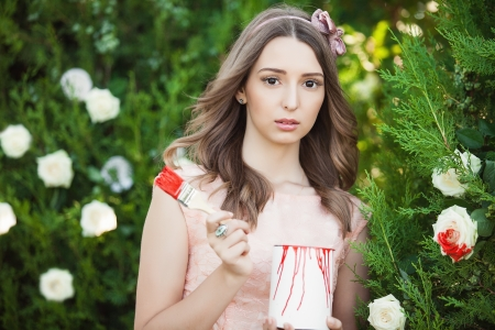 meaningless: Fancy Daydreaming Woman with brush paint on the flowers. Surrealism Stock Photo