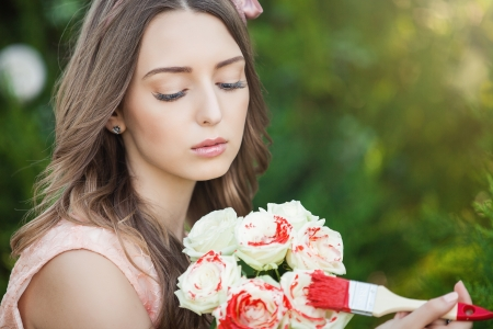 surrealism: Fancy Daydreaming Woman with brush paint on the flowers. Surrealism Stock Photo