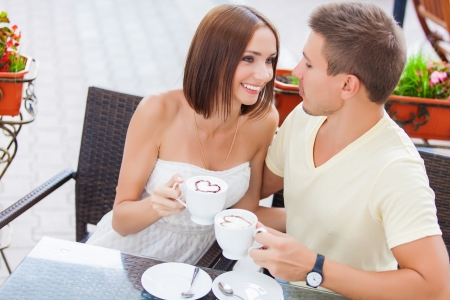 Happy couple in love drinking coffee and looking at each other photo