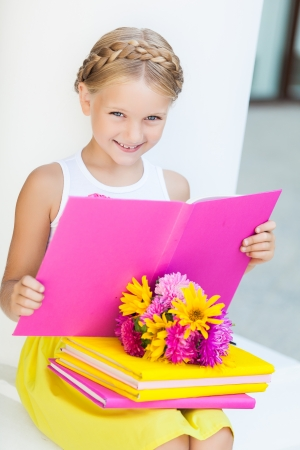 Education - funny girl with a books and flowers photo