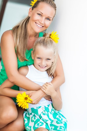 Family portrait cute little girl and cheerful mom photo