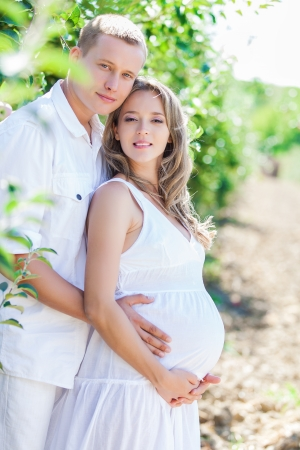 Family, husband and pregnant wife posing in a green apple garden Imagens