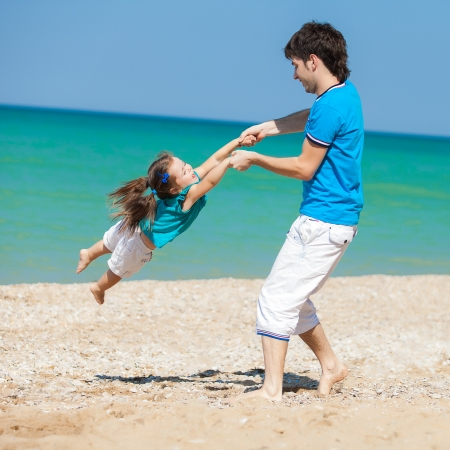 Father and daughter playing together at the beach photo