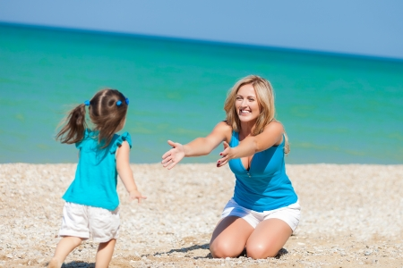 little girl and her mother have a good time at the beach