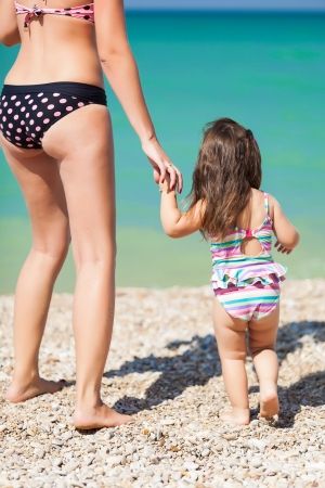 little girl and her mother have a good time at the beach photo