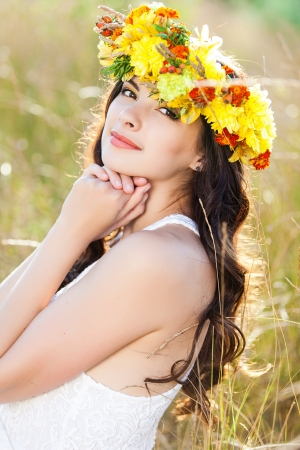 Closeup portrait of beautiful young woman with flower wreath on her head against summer field photo