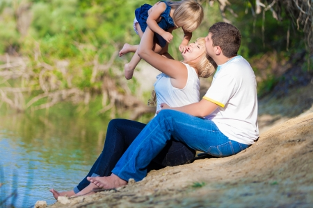 happy young family spending time outdoor on a lake photo