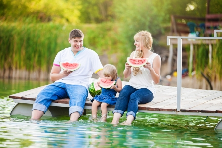 happy young family on picnic in the green park with lake photo